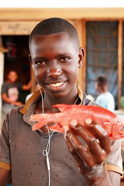 Fischmarkt Junge mit Fisch