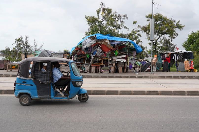 Dar Es Salam Straßenstand und Tuktuk